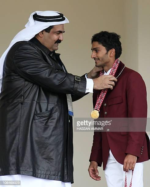 Qatari Emir Sheikh Hamad bin Khalifa al-Thani decorates Abdulla Ali al-Ejail with the gold medal after winning with his fellow teammates Mohammed...