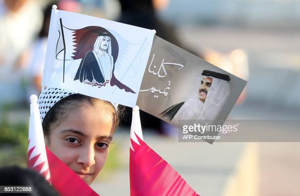 A Qatari girls wears flags bearing the portrait of the Emir of Qatar Sheikh Tamim bin Hamad bin Khalifa alThani as Qataris gather in the streets of...