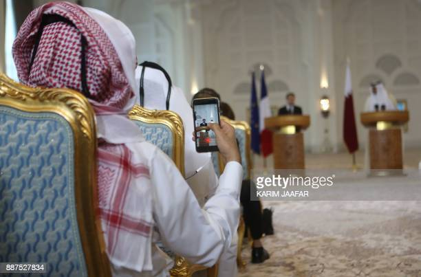A Qatari man takes a picture o Emir Sheikh Tamim bin Hamad alThani and French President Emmanuel Macron giving a press conference following the...