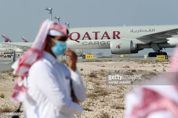Qatari men walk next to a Qatar Airways cargo airplane on the tarmac of Hamad International Airport near the capital Doha, as the first commercial...