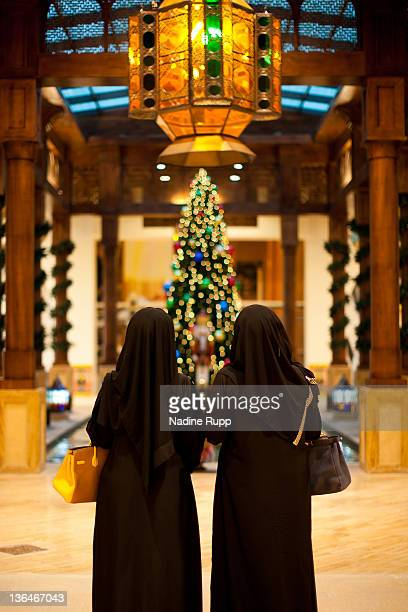 Qatari people in their traditional clothes called abaya look at a christmas tree inside the still under construction manmade peninsula project called...