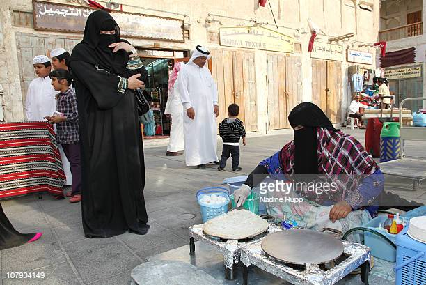 Qatari people in their traditional clothes called dishdasha and abaya are pictured at Souq Waqif on December 24 2010 in Doha Qatar The Souq Waqif a...