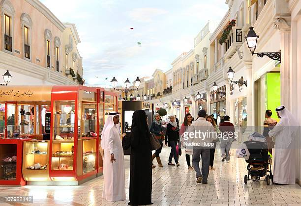 Qatari people in their traditional clothes called dishdasha and abaya are pictured at Villagio shopping mall on December 29 2010 in Doha Qatar The...