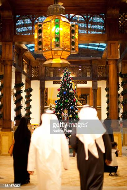 Qatari people in their traditional clothes called dishdasha and abaya look at a christmas tree inside the still under construction manmade peninsula...