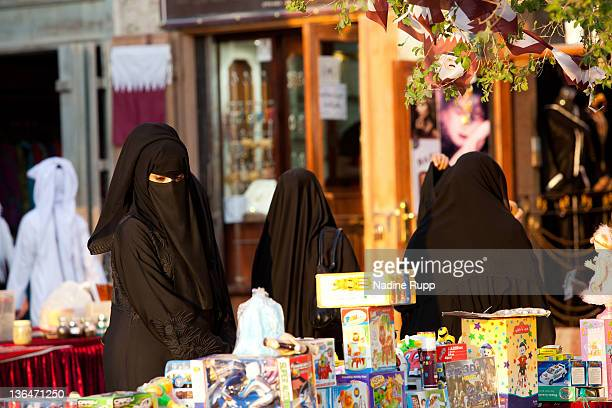 Qatari people in their traditional clothes called dishdasha and abaya are pictured at Souq Waqif at Souq Waqif on December 24 2011 in Doha Qatar The...
