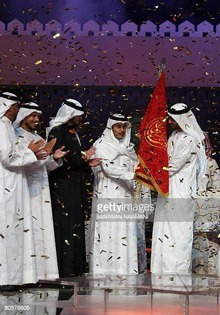 Qatari poet Khalil alShebrami alTamimi winner of 'One Million Dirhams Poet' TV program receives the winning flag from United Arab Emirates Foreign...