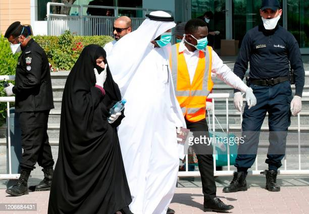 Qatari police stand outside a hotel in Doha as a medical worker walks alongside people wearing protective masks over fears of coronavirus on March 12...