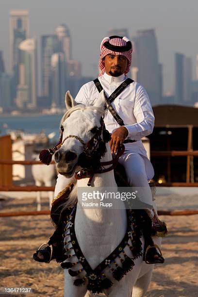 Qatari policeman rides Araber horses in his traditional clothes called dishdasha at Souq Waqif on December 24 2011 in Doha Qatar The FIFA World Cup...