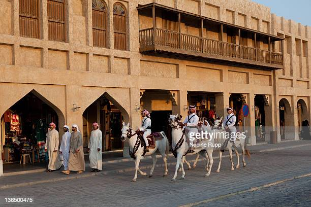 Qatari policemen in their traditional clothes called dishdasha ride Araber horses at Souq Waqif on December 26 2011 in Doha Qatar The The FIFA World...