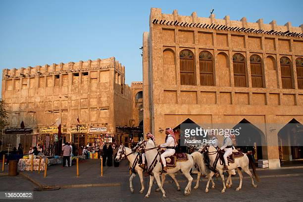 Qatari policemen in their traditional clothes called dishdasha ride Araber horses at Souq Waqif on December 26 2011 in Doha Qatar The FIFA World Cup...