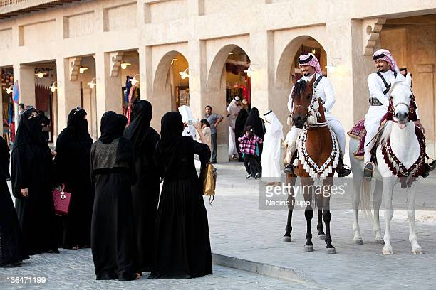 Qatari policemen ride Araber horses in their traditional clothes called dishdasha at Souq Waqif on December 24 2011 in Doha Qatar The FIFA World Cup...