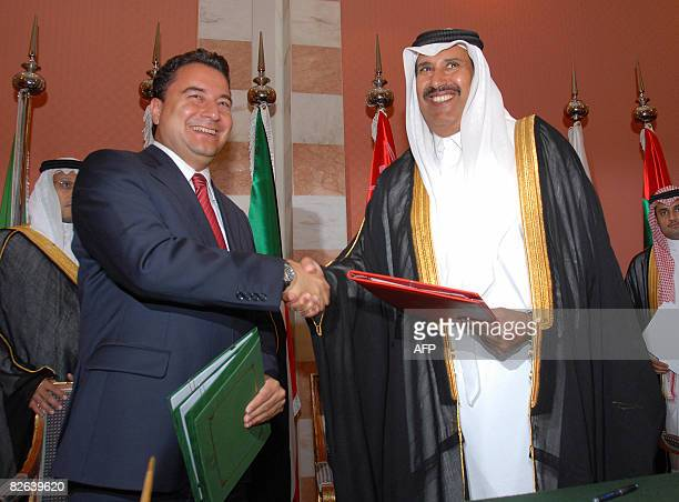 Qatari Prime Minister Sheikh Hamad bin Jassem alThani shakes hands with Turkish Foreign Minister Ali Babacan after signing an agreement to boost ties...