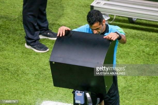Qatari referee Abdulrahman al-Jassim checks the VAR during the 2019 FIFA Club World Cup Final football match between England's Liverpool and Brazil's...