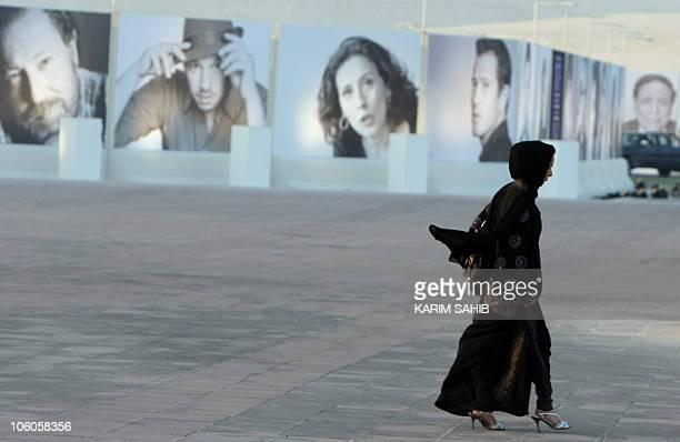 A Qatari woman walks past pictures of actors attending Doha's second Tribeca Film Festival and members of the jury including US actor Robert De Niro...