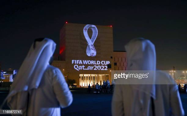 Qataris gather at the capital Doha's traditional Souq Waqif market as the official logo of the FIFA World Cup Qatar 2022 is projected on the front of...