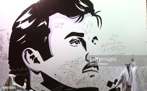 Qataris write comments on a wall bearing a portrait of Qatar's Emir Sheikh Tamim bin Hamad Al Thani in Doha on July 6 2017 / AFP PHOTO / KARIM JAAFAR