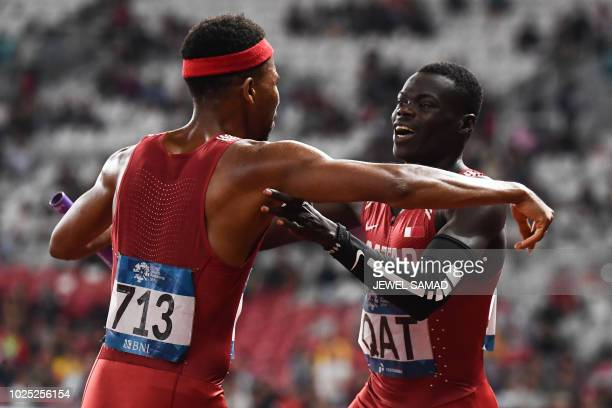 Qatar's Abdalelah Hassan and Abderrahman Samba celebrate winning the final of the men's 4x400m relay athletics event during the 2018 Asian Games in...
