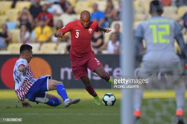 Qatar's Abdelkarim Hassam is marked by Paraguay's Hernan Perez during their Copa America football tournament group match at Maracana Stadium in Rio...