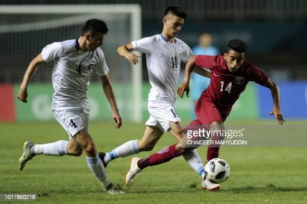 Qatar's Ahmed Alsaadi fights for the ball with Uzbekistan's Ikromjon Alibaev and Akramjon Komilov during the men's football preliminary Group B match...