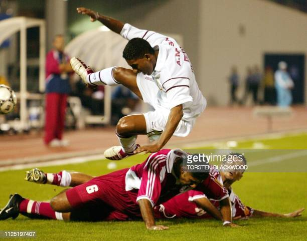 Qatar's Ahmed Mohd Mosa leaps over Lebanon's Faissal Antar and Bilal Hajo during the first round of the 14th Asian Games in Yangsan 28 September 2002...