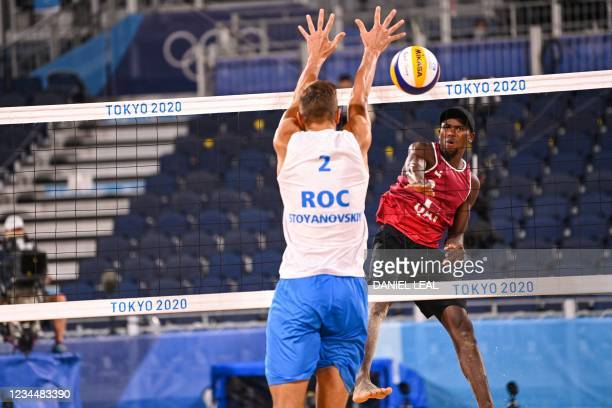 Qatar's Ahmed Tijan attempts a shot past Russia's Oleg Stoyanovskiy in their men's beach volleyball semi-final match between Qatar and Russia during...