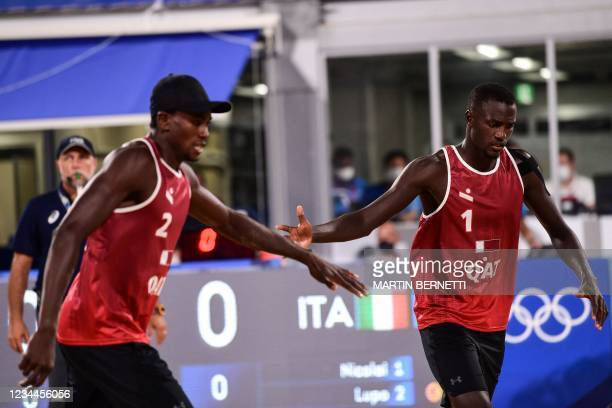 Qatar's Ahmed Tijan gestures to partner Cherif Younousse in their men's beach volleyball quarter-final match between Qatar and Italy during the Tokyo...