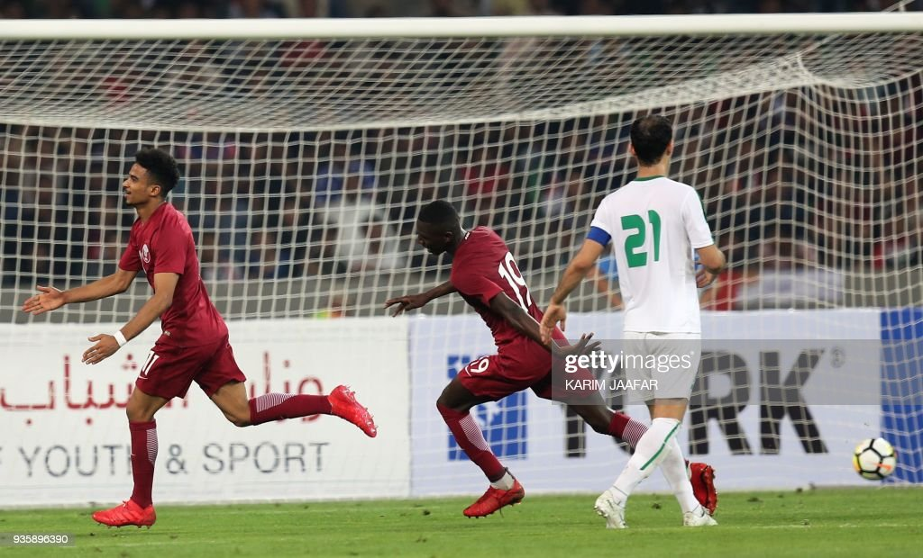 Qatar's Akram Hassan Afif (L) celebrates with his teammate Almoez Ali Abdulla after scoring a goal during the international friendly football match between Iraq and Qatar at the Basra Sports City Stadium in Basra on March 21, 2018. /