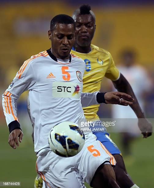 Qatar's Al-Gharafa player Djibril Cisse fights for the ball with Naif Al-Qadi of Saudi Arabia's Al-Shabab during their AFC Champions League soccer...