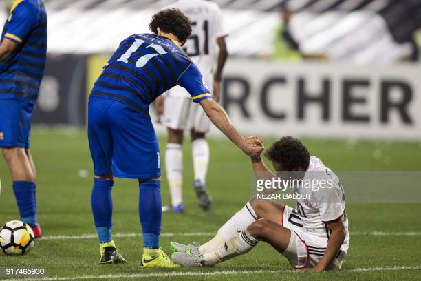 Qatar's alGharafa's Ahmed Alaaeldin Abdelmotaal helps alJazira's Mohamed Jamal get off the ground during the AFC Champions League Round 1 Group Match...