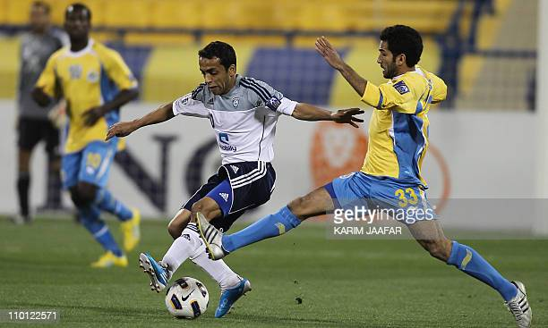 Qatar's alGharrafa player Ahmed Fris vies for the ball with Saudi's alHilal player Mohammed alShalhoub during their AFC Champions League soccer match...
