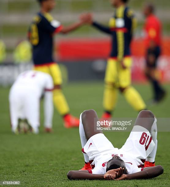 Qatar's Almoez Ali lies dejected on the field after the FIFA Under20 World Cup football match between Qatar and Colombia in Hamilton on May 31 2015...