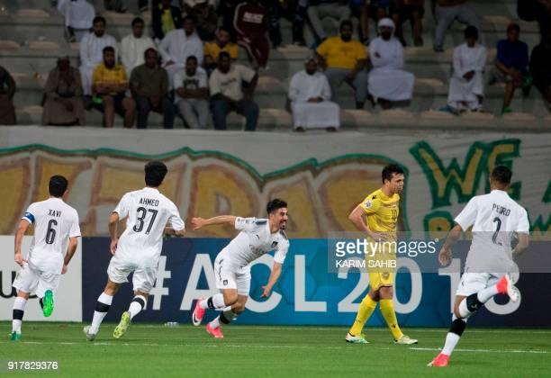 Qatar's alSadd player Baghdad Bounedjah celebrates with his teammates after scoring a goal during the AFC Champions League group stage football match...