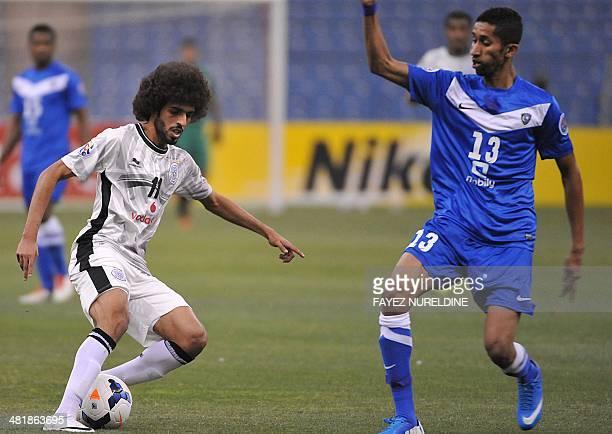 Qatar's Al-Sadd player Hassan al-Haidos dribbles the ball as Saudi's Al-Hilal player Salem Al-Faraj defends during their AFC Champions League group D...