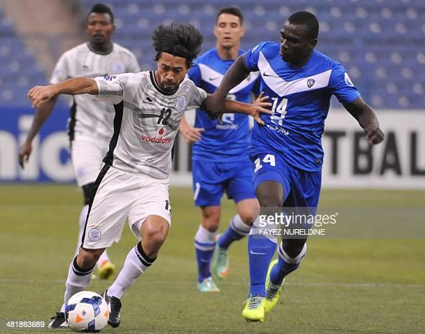 Qatar's Al-Sadd player Rodrigo Tabata dribbles the ball as Saudi's Al-Hilal player Castillo tries to defend during their AFC Champions League group D...