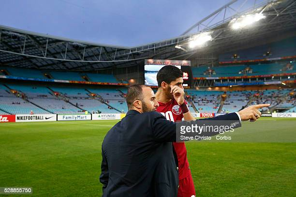 Qatar's coach Djamal Belmadi gives Karim Boudiaf some last minute instructions before the game against Qatar at Stadium Australia Sydney Australia...