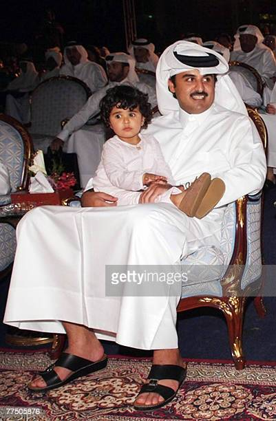 Qatar's Crown Prince and President of the Qatar Olympic Committee Sheikh Tamim bin Hamad alThani sits holding his daughter Mayyasa whilst attending a...