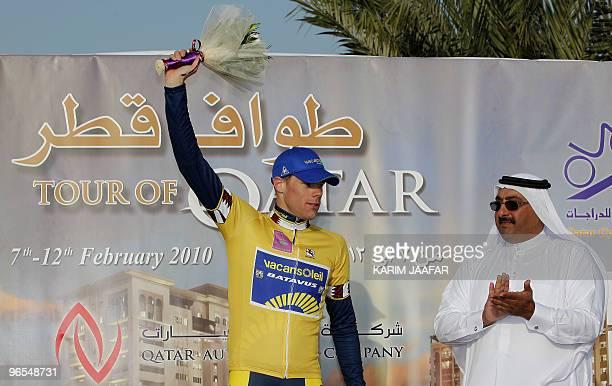 Qatar's cycling federation president, Sheikh Khaled bin Ali al-Thani, applaudes as Vacansoleil team rider Wouter Mol of the Netherlands celebrates in...