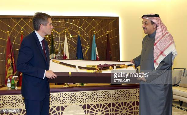 Qatar's Defence Minister Khalid bin Mohammed alAttiyah presents a gift sword to his British counterpart Gavin Williamson in the capital Doha on...