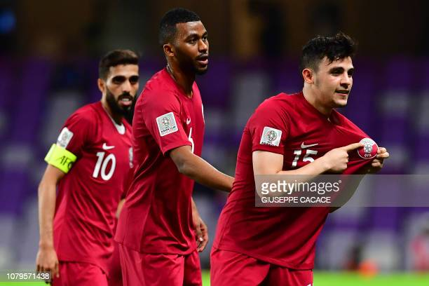Qatar's defender Bassam al-Rawi points to his jersey badge as he celebrates the first goal of the match during the 2019 AFC Asian Cup group E...