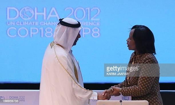 Qatar's deputy Prime minister and 18th Conference of the Parties president Abdullah bin Hamad AlAttiyah shakes hands with South Africa's Foreign...