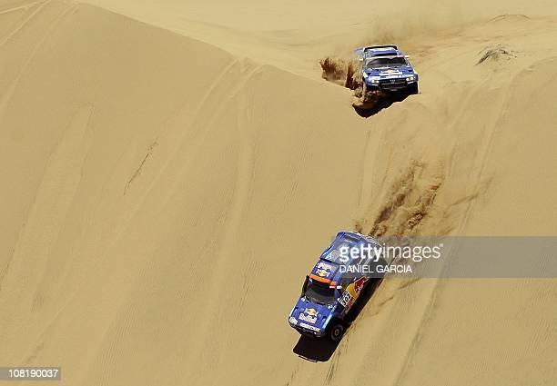 Qatar's driver Nasser AlAttiyah steers his Volkswagen with German codriver Timo Gottschalk followed by Spain's driver Carlos Sainz with codriver...