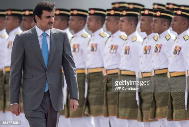 Qatar's Emir Sheik Tamim bin Hamad alThani inspects a ceremonial guard of honour during a welcoming ceremony at the Parliament in Kuala Lumpur on...