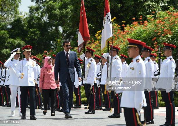 Qatar's Emir Sheik Tamim bin Hamad alThani inspects the guard of honour followed by Singapore President Halimah Yacob during a welcoming ceremony at...