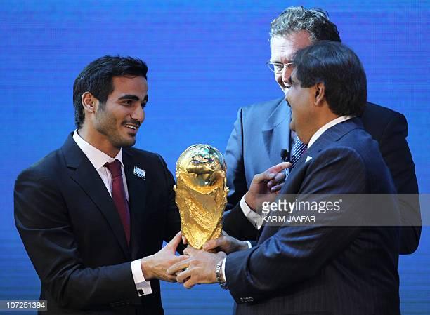 Qatar's Emir Sheikh Hamad bin Khalifa alThani and his son Sheikh Mohammed bin Hamad alThani chairman of Qatar 2022 bid committee hold the World Cup...