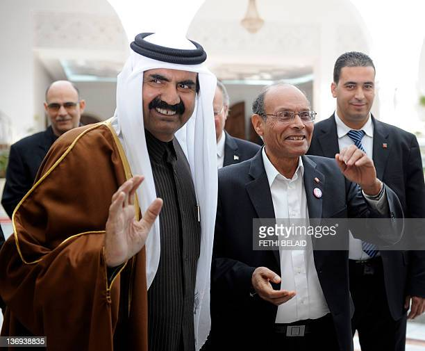 Qatar's Emir Sheikh Hamad bin Khalifa al-Thani is welcomed by Tunisian President Moncef Marzouki upon his arrival on January 13, 2012 in Tunis....