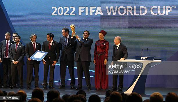 Qatar's Emir Sheikh Hamad bin Khalifa alThani raises the World Cup trophy as he stands with members of the Qatar 2022 bid committee and FIFA...