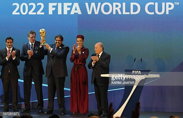 Qatar's Emir Sheikh Hamad bin Khalifa al-Thani raises the World Cup trophy as he stands with his wife Sheikha Moza, their son Sheikh Mohammed,...
