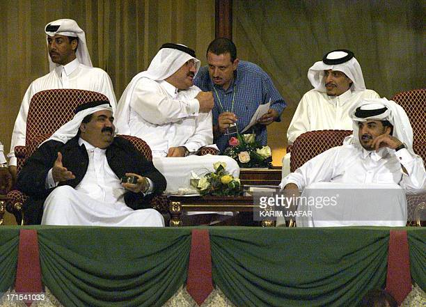 Qatar's Emir Sheikh Hamad bin Khalifa alThani speaks to his son Sheikh Tamim bin Hamad as they attend the second round of the Qatar Open with other...