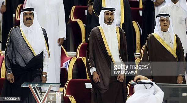 Qatar's Emir Sheikh Hamad bin Khalifa alThani stands with his son Sheikh Jassim bin Hamad alThani and new Asian Football Confederation President...