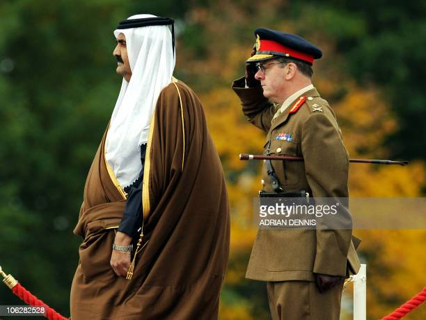 Qatar's Emir Sheikh Hamad bin Khalifa alThani takes the salute as he stands beside Commandant General Marriot at The Royal Military Academy in...